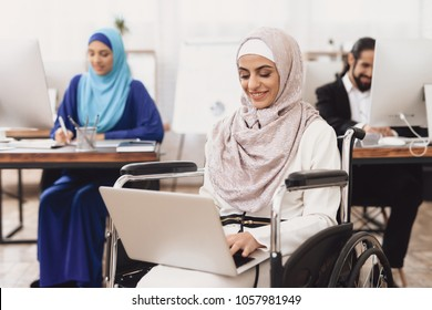 Disabled arab woman in hijab in wheelchair working in office. Woman is working on laptop.