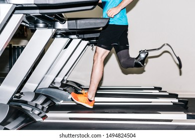 Disabled athlete with leg prosthesis running on a treadmill in the gym.