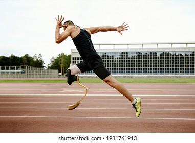 disabled athlete runner on prosthetic leg on track of stadium
