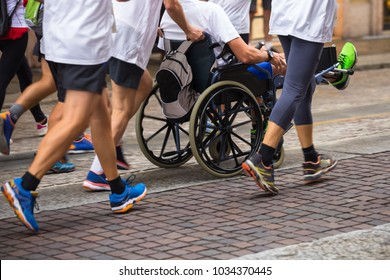 Disabled Athlete in a Sport Wheelchair during Marathon Helped by Runners.