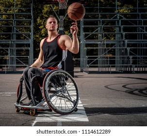 Disabled basketball player in a wheelchair spinning basketball on his finger on open gaming ground.