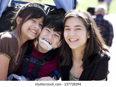 Disabled biracial boy in wheelchair surrounded by his bigger sisters, smiling. Child has cerebral  palsy.