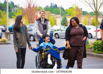 Disabled biracial boy in wheelchair walking along city street with father, siblings and caregiver, holding hands