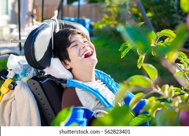 Disabled biracial ten year old boy in wheelchair relaxed and laughing  in back yard