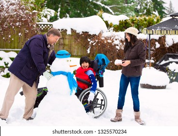 Disabled biracial young boy in wheelchair building a snowman with father and sister during winter after heavy snowfall