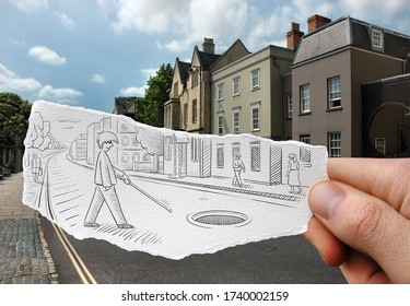 Disabled blind man crossing street drawn on a hand held piece of paper with houses and apartments in the photo background. Mixed media image
