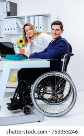 disabled businessman in wheelchair greeting his female colleague