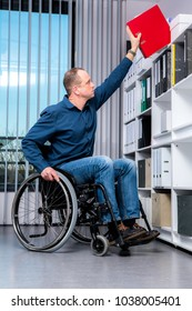 disabled businessman in wheelchair taking a folder in the office