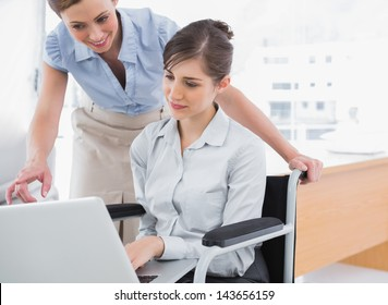 Disabled businesswoman showing co worker her laptop in the office