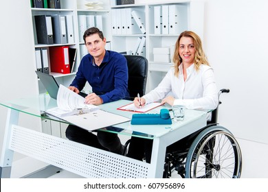 disabled businesswoman in wheelchair and her colleague in the office