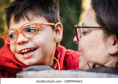 disabled child in his mother's arms laughing, hugging, smiles ... scene full of maternal love. The mother whispers things in her ear. Have fun in city park in winter.
