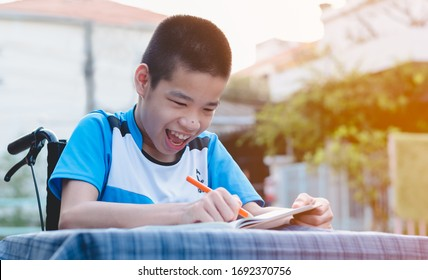 Disabled child on wheelchair enjoying the training of hand and finger muscles through writing with a big stick, Special children's lifestyle,Life in the education age, Happy disability kid concept.