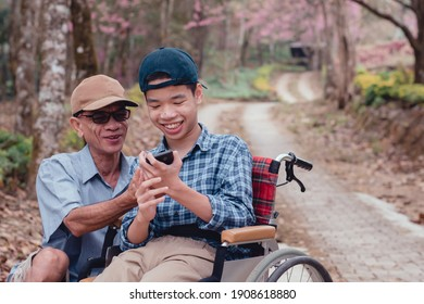 Disabled child on wheelchair and father in the city park, They have fun with selfie by smart phone, Life in the education age of special children,Happy disability kid travel in family holiday concept.
