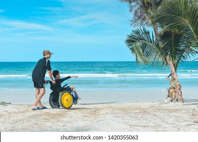 Disabled child on wheelchair and his dad, Blue sea background, Beach in Thailand, Father helped him to get closer to nature, Life in the education age of special Children, Happy disabled kid concept.