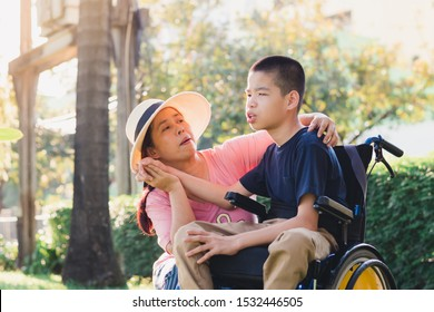Disabled child on wheelchair and mom in the outdoor park, His mother sent love through the eyes and gentle hands touch, Life in the education age of special children, Happy disability kid concept.
