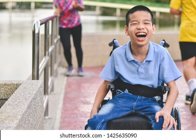 Disabled child on wheelchair is play and learn in the outdoor park like other people, Life in the education age of special children, Happy disability kid concept.