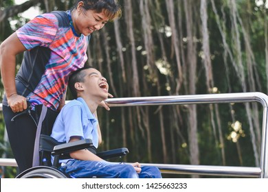 Disabled child on wheelchair is playing in the outdoor park like other people, He has a young aunt to take care of closely, Life in the education age of special children, Happy disability kid concept.
