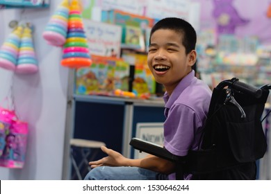 Disabled child on wheelchair trying begged parents to buy a toy for him in Books and toys fair,Special children's lifestyle,Life in the education age of special need kids,Happy disability kid concept.