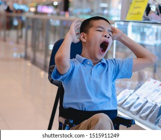Disabled child on wheelchair yawning because of sleepiness while waiting for parents to run errands in the IT Mall, Life in the education age of special need kids, Happy disability kid concept.