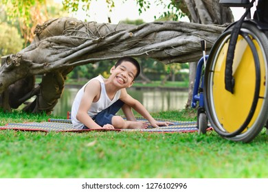Disabled child sit on mat that is paved on the lawn in the park with fun. Beside each other, his wheelchair is parked.