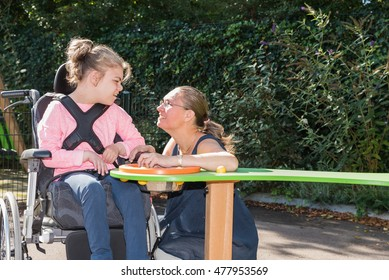 A disabled child in a wheelchair being cared for by a special needs carer / Working with disability