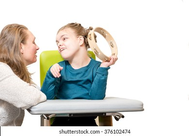 Disabled child in a wheelchair having music therapy together with a special needs carer / Working with mentally handicapped children