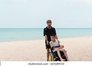 Disabled child in wheelchair and his father on the sea beach, Blue sky background, He spend a holiday with happiness travel, Life in education age of disabled children, Happy disability kid concept.