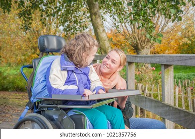 A disabled child in a wheelchair relaxing outside together with a voluntary care worker.