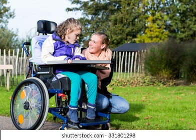Disabled child in wheelchair relaxing outside with a care assistant/ Working with disability