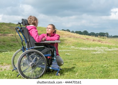 Disabled child in a wheelchair relaxing outside together with a special needs carer / Working with mentally and physically handicapped children
