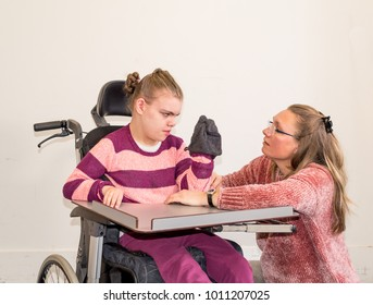 A disabled child in a wheelchair together with a voluntary care worker