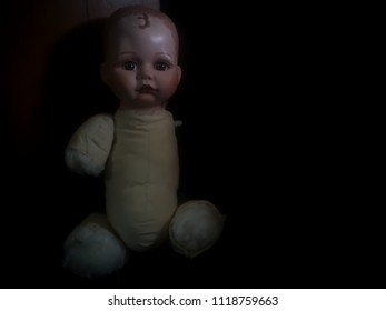disabled creepy doll sit in the dark room in high contrast