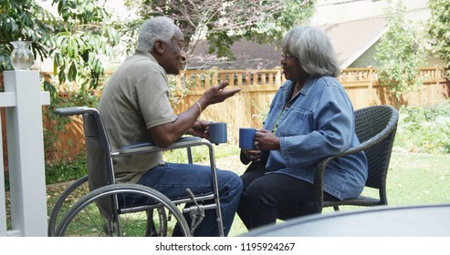 Disabled elderly African man talking with wife in the backyard