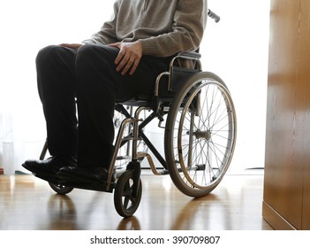 disabled elderly sitting in a wheelchair in the his room