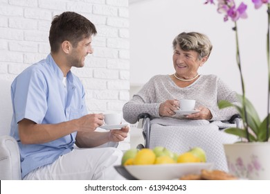 DIsabled elderly woman in inursing home with young professional caregiver