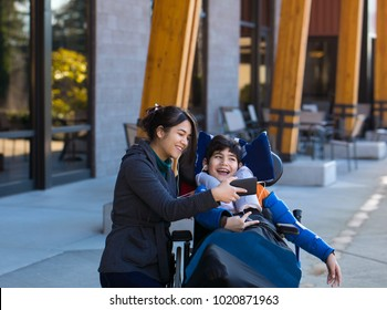 Disabled eleven year old biracial boy in wheelchair watching video on smartphone with his two caregivers outdoors