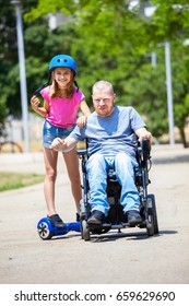 Disabled father with his daughter on hoverboard having fun at the park