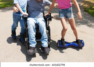 Disabled father on the wheelchair playing with children.