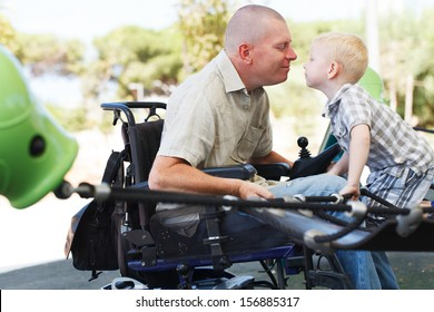 Disabled Father play with his little son on the playground