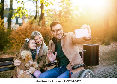 Disabled father in wheelchair enjoying with his daughter, wife and dog outdoors in park, and taking selfie photo.