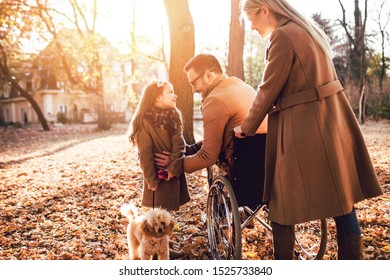 Disabled father in wheelchair enjoying with his daughter and wife outdoors in autumn park.