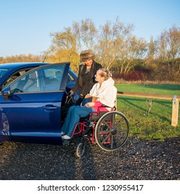 A Disabled Female in her Wheelchair and her Carer getting into a Mobility Car at Park