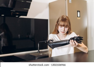 disabled girl checking her matal prosthetci arm, close eup photo. copy space .girl studing her artificial limb while sitting in the room