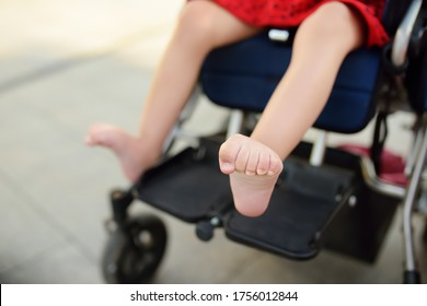Disabled girl sitting in wheelchair. Close up photo of her legs spasticity muscles . Child cerebral palsy. Disability. Inclusion. Family with disabled kid. Family with disabled kid.
