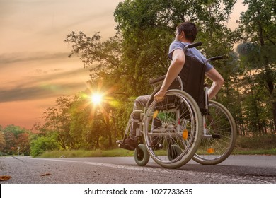 Disabled or handicapped young man on wheelchair in nature at sunset.