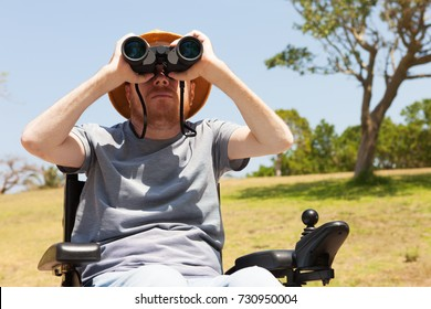 Disabled man with binocular sitting on the wheelchair.