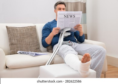 Disabled Man With Crutches Sitting On Sofa Reading Newspaper