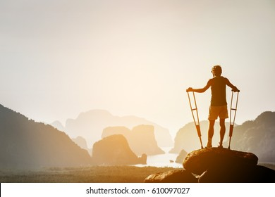 Disabled man with crutches stands on a big rock and looking at great view to islands and mountains. Space for text. Winner pose
