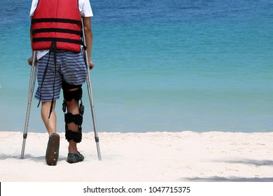 Disabled man with crutches while travel on the beach.