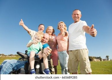 Disabled Man with family outside showing thumbs up.